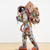 Refugee Astronaut II 2016 Fibreglass mannequin, Dutch wax printed cotton textile, net, possessions, astronaut helmet, moon boots and steel baseplate 186 x 87 x 103 cm © Yinka Shonibare MBE Courtesy the artist and James Cohan Gallery, New York, Photographer: Stephen White